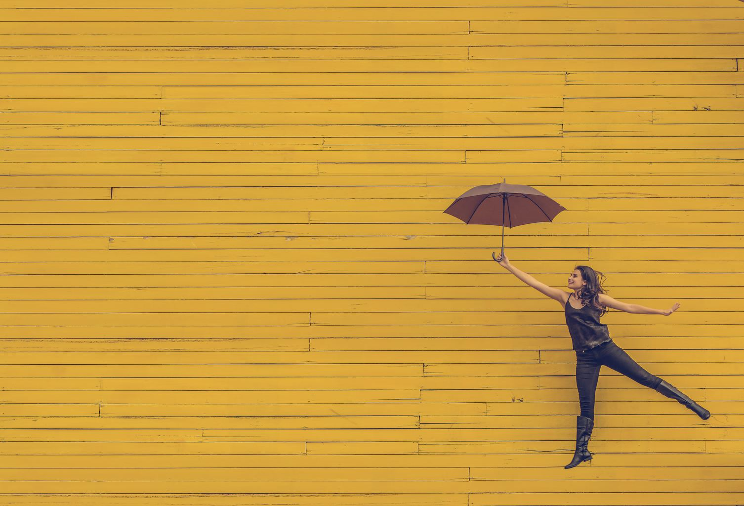 Chica saltando con paraguas delante de fachada amarilla