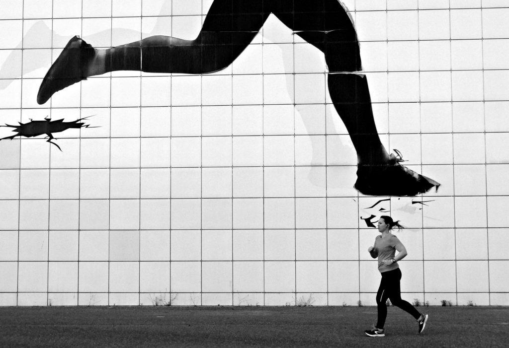 Chica corriendo con fachada de pies de corredor encima de su cabeza