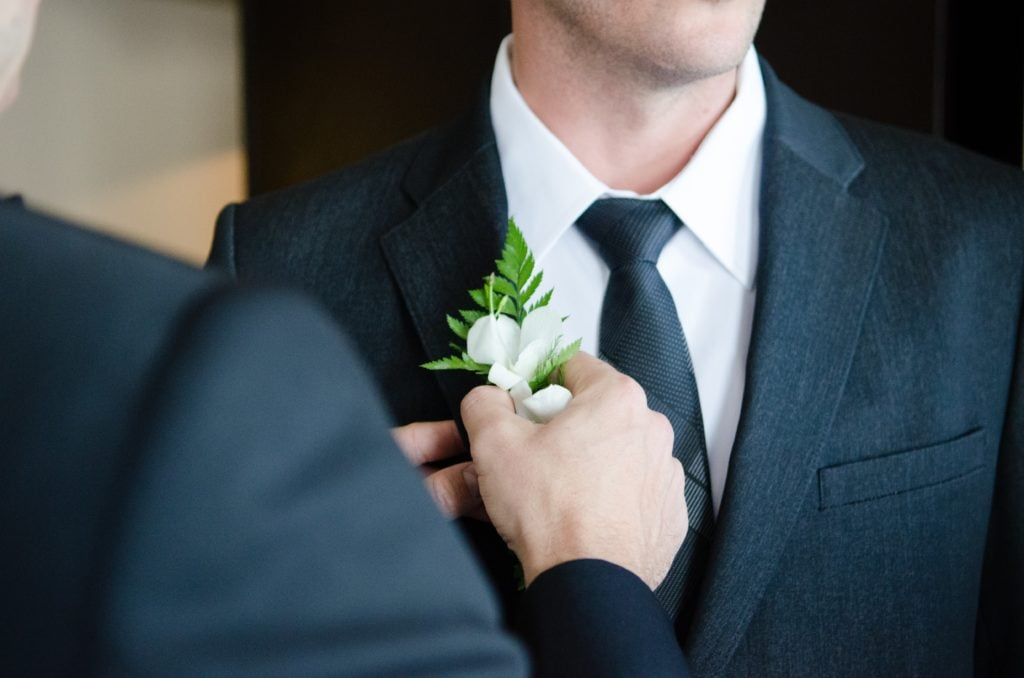 Familiar colocando flor en la solapa al novio
