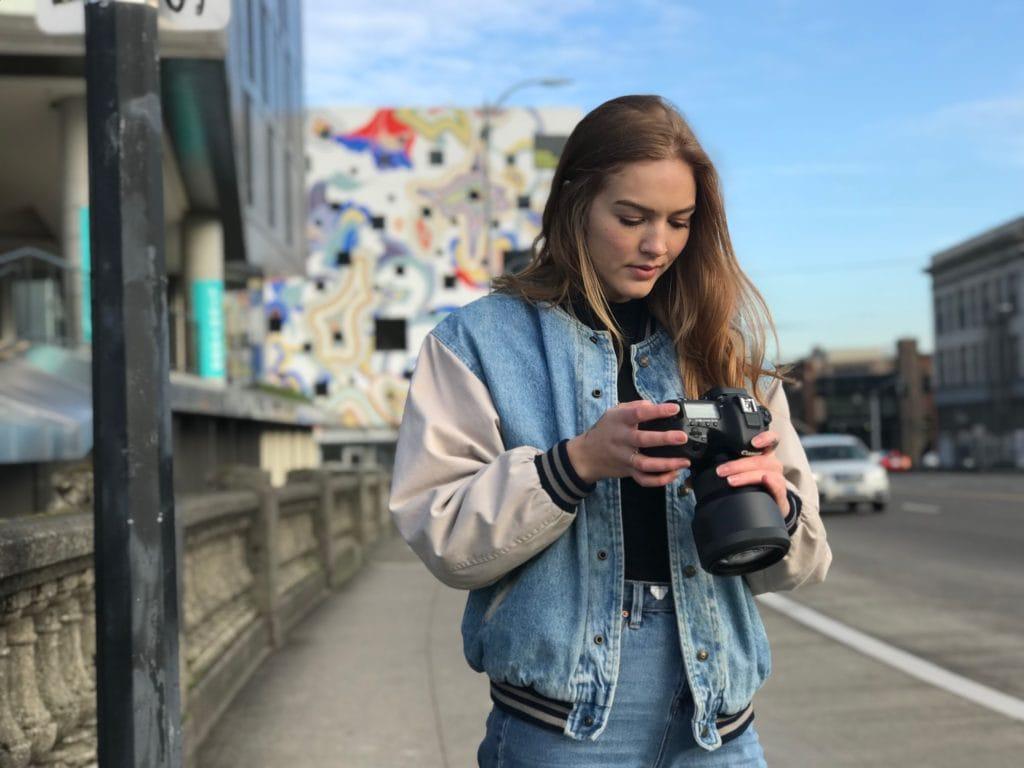 Fotógrafa mirando cámara en la calle