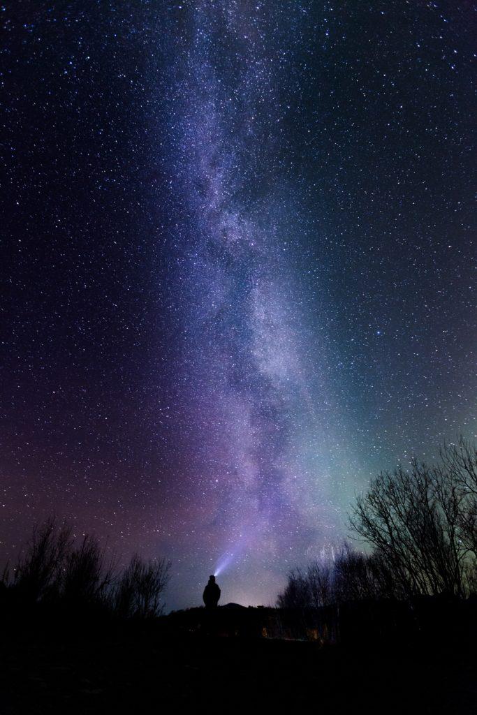 fotografía nocturna con cielo de estrellas y silueta con frontal