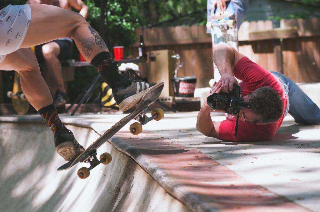 Fotógrafo tumbado en el suelo para fotografiar a un skater
