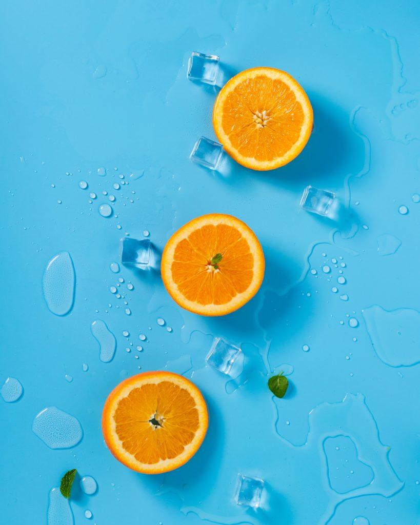 Naranjas sobre fondo azul y hielo