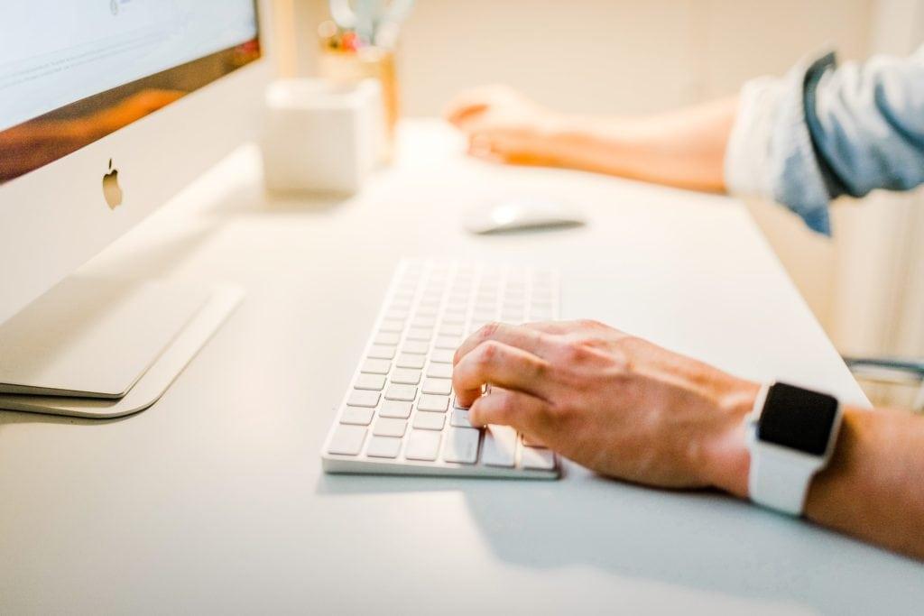 Teclado y pantalla Mac con alguien escribiendo