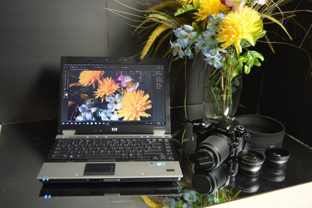 Ordenador con Photoshop en pantalla y al lado cámara y objetivos