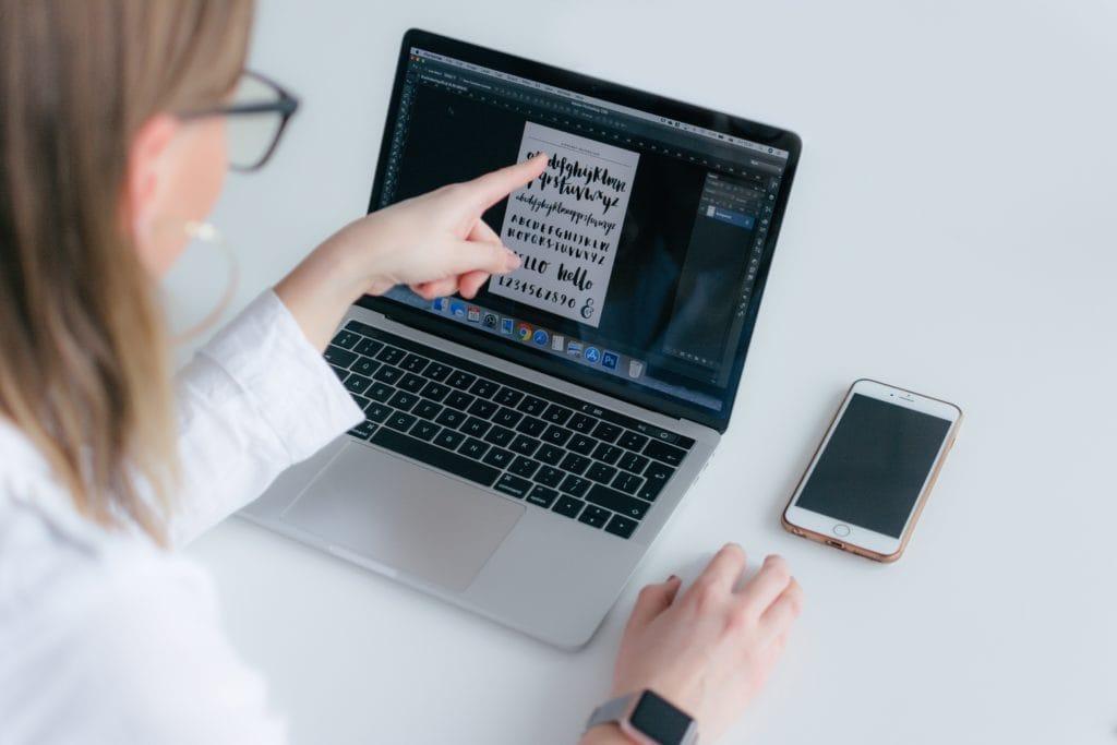 Mujer eligiendo tipografía en un portátil