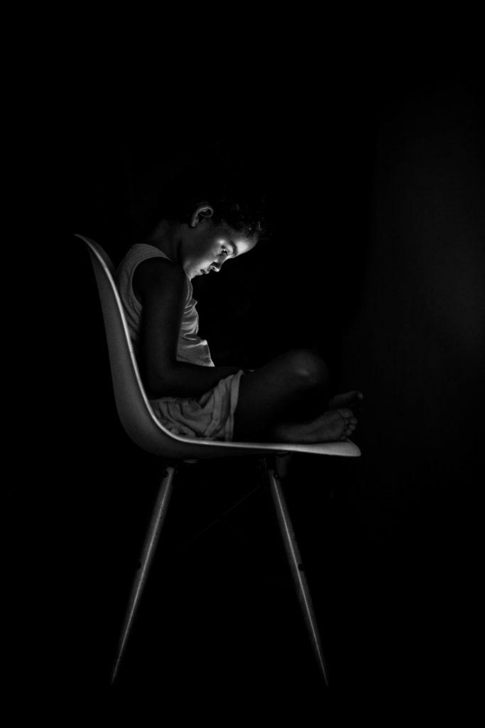 niña sentada en silla a oscuras con luz de pantalla