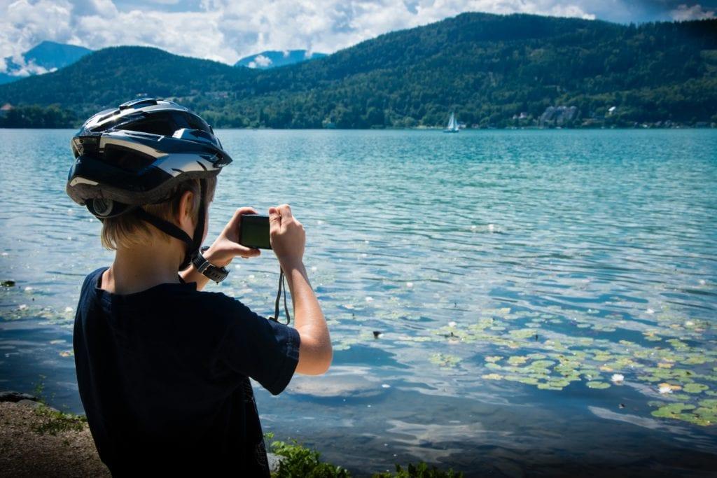 Niño haciendo fotos en lago