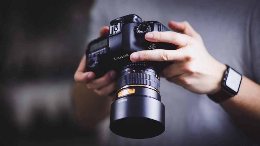 Camara profesional en manos de un fotógrafo