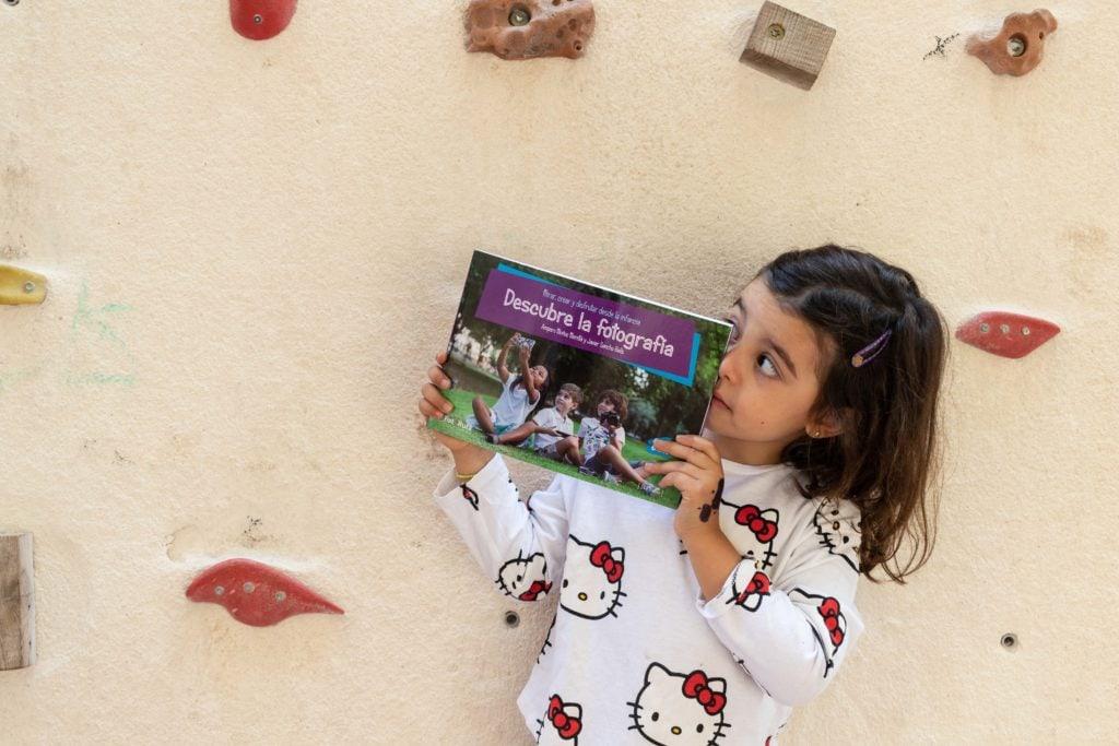 Niña con el libro Descubre la fotografía en las manos