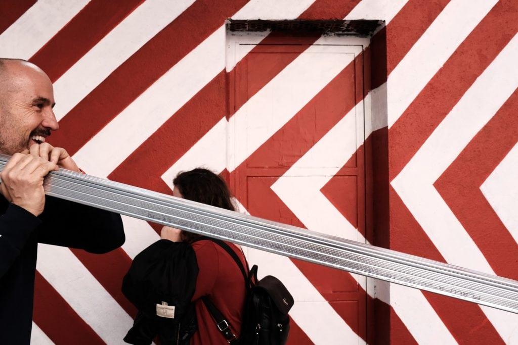 Escena callejera con fachada de líneas rojas y blancas