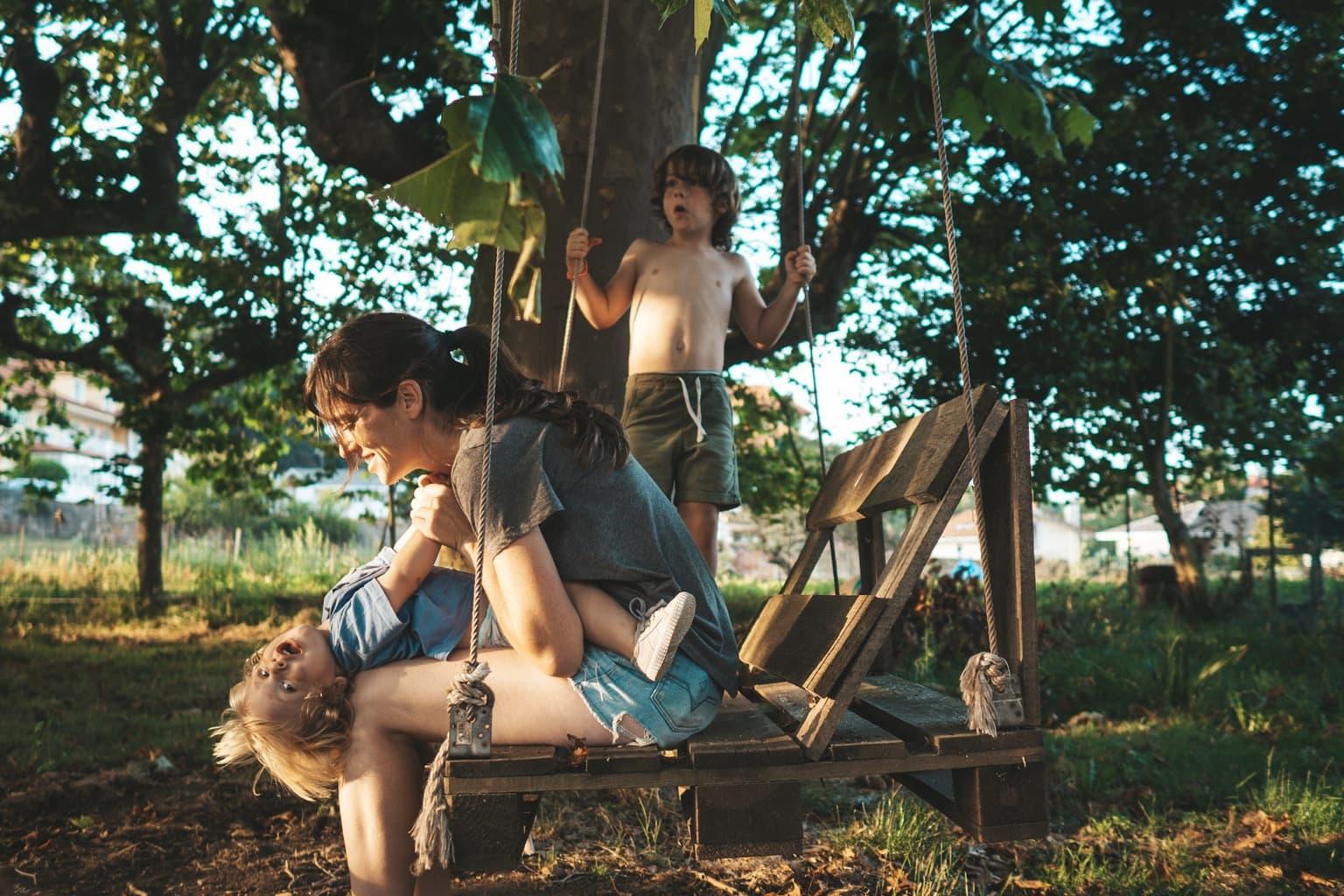 madre en columpio de madera con sus hijos