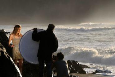 fotógrafos iluminando a modelo con reflector en la playa