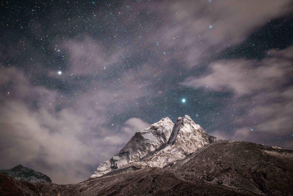 Fotografía de montaña de noche rodeada de estrellas