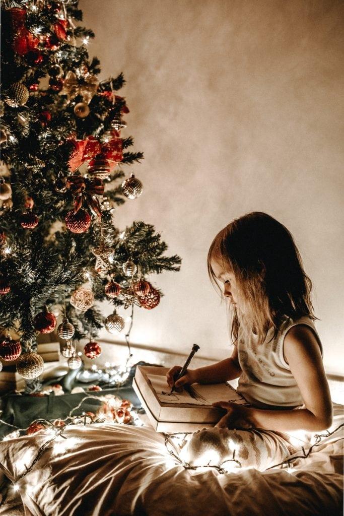 Niña junto a árbol de Navidad