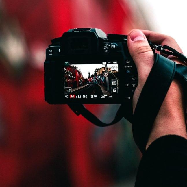camara en mano de fotógrafo con pantalla y datos