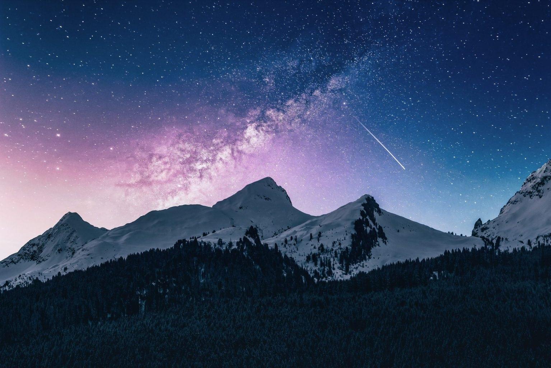Montañas nevadas con cielo estrellado y estrella fugaz