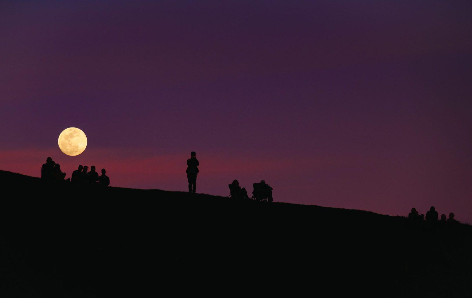 Gente observando y fotografiando la luna