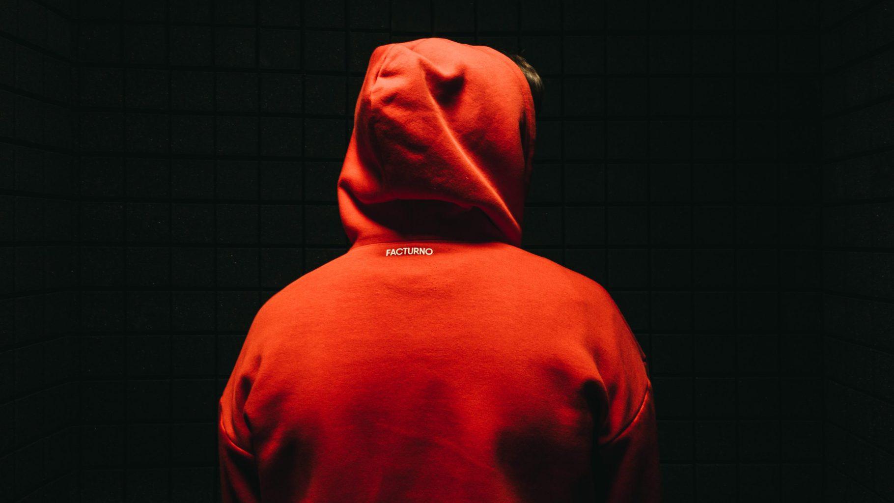 Retrato de espaldas de alguien con capucha roja