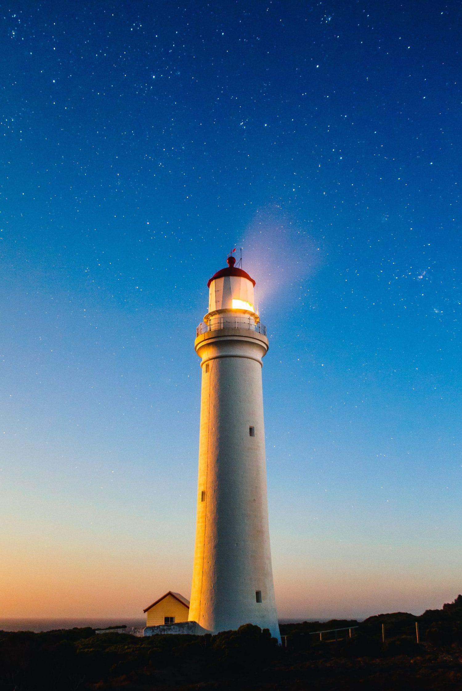Faro en larga exposición con cielo de estrellas