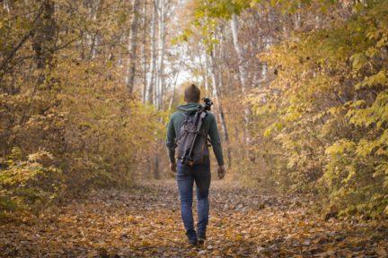 Fotógrafo caminando por un bosque con mochila y trípode a la espalda