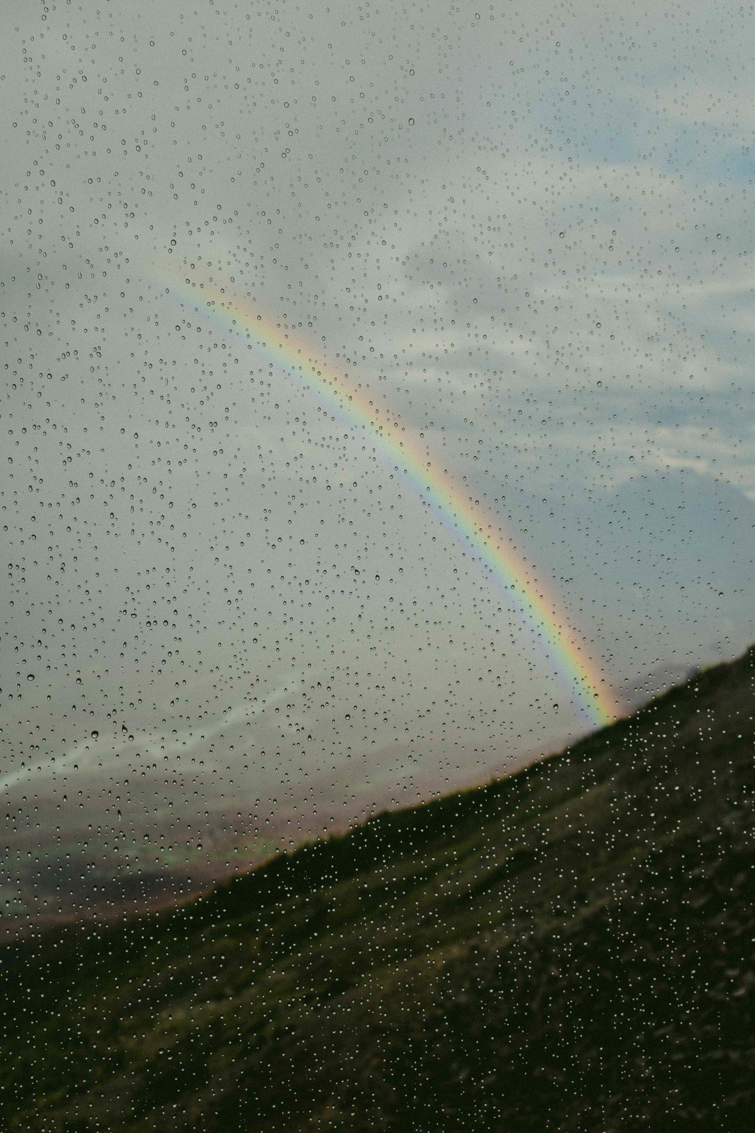 Arcoíris visto desde detrás de cristal con gotas de agua