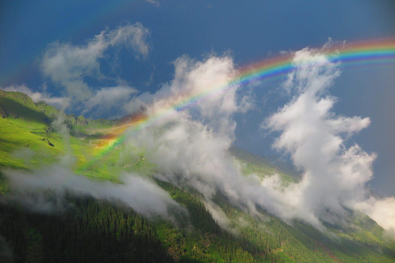 Arcoíris en paisaje con nubes