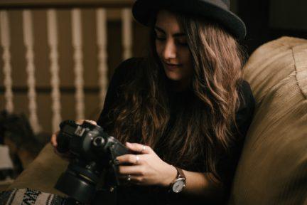 Chica con cámara sentada en un sofá