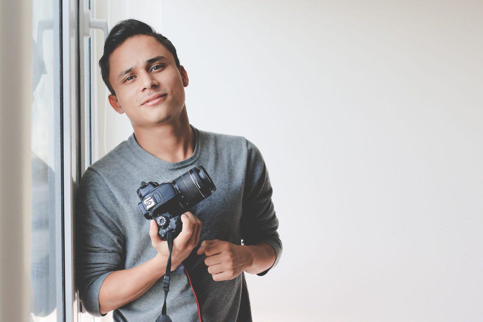 Chico con cámara en la mano junto a ventana