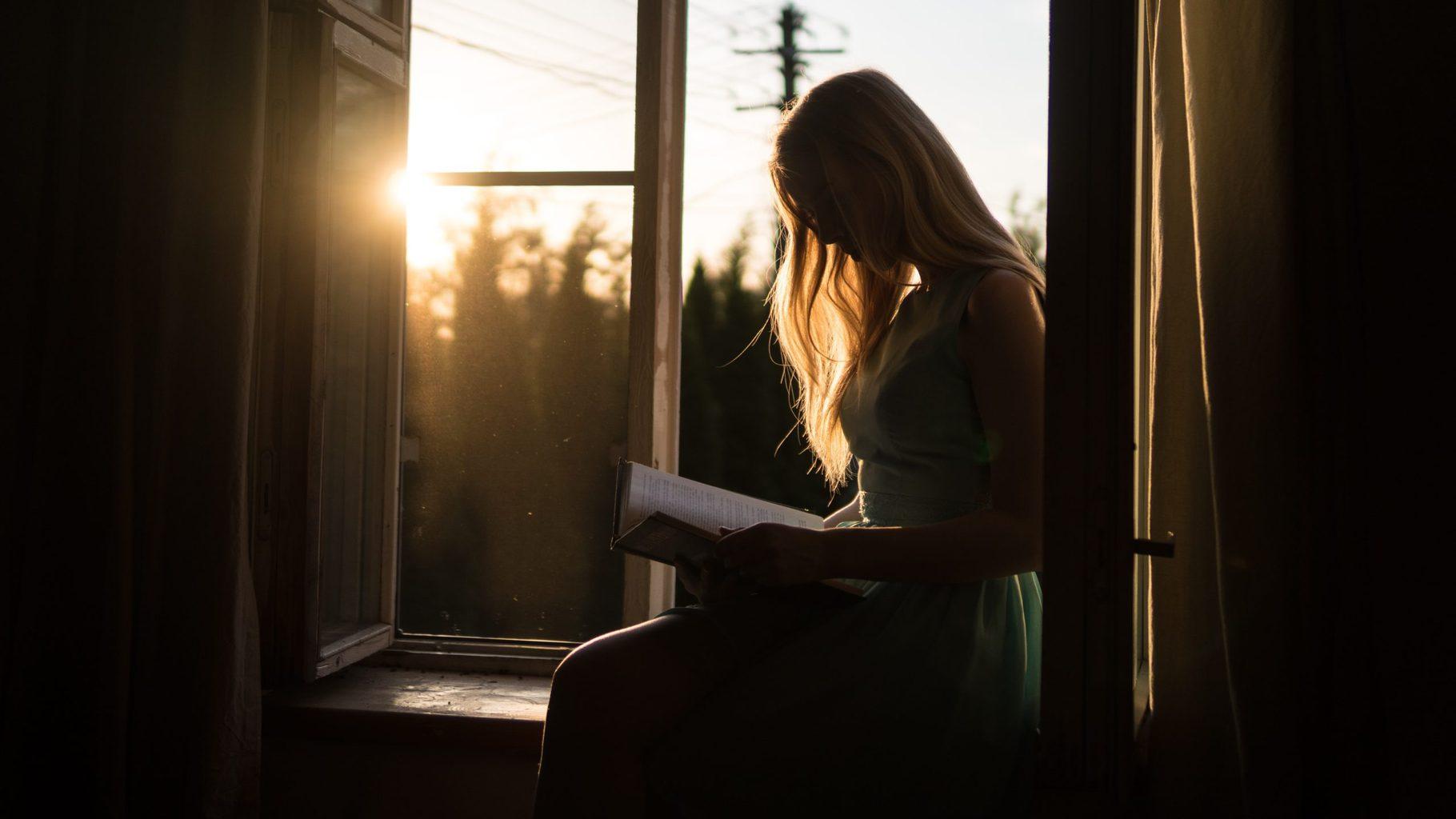 mujer leyendo en ventana