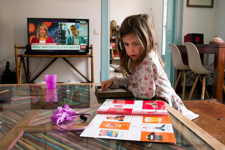 niña con noticias en tv al fondo
