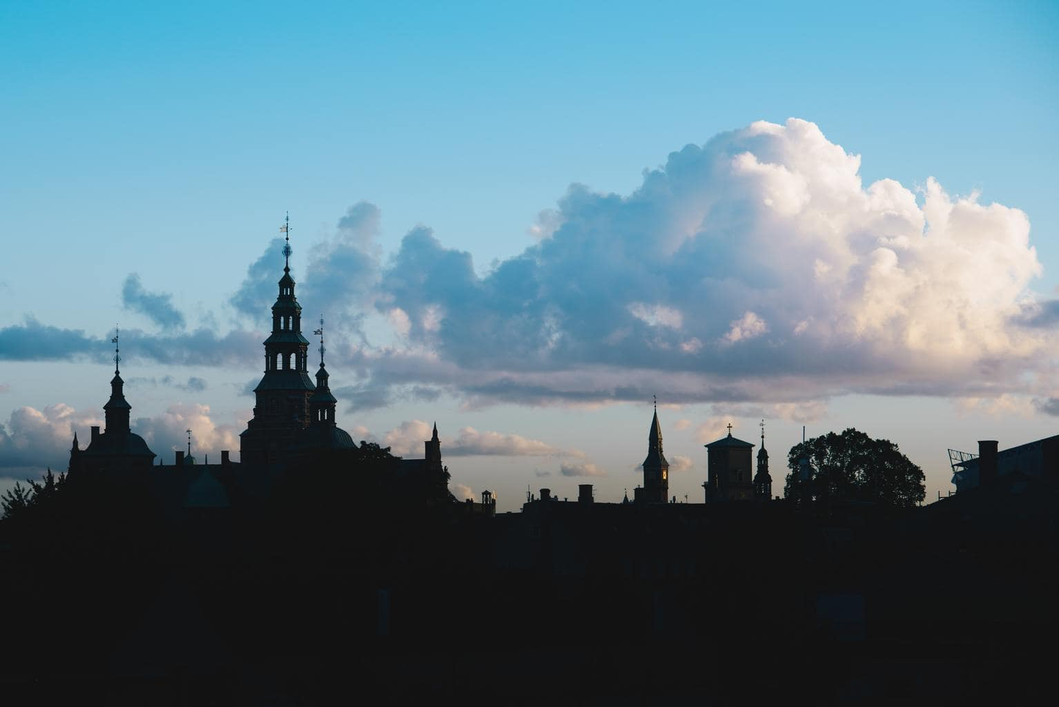 ciudad a contraluz con nubes en el cielo