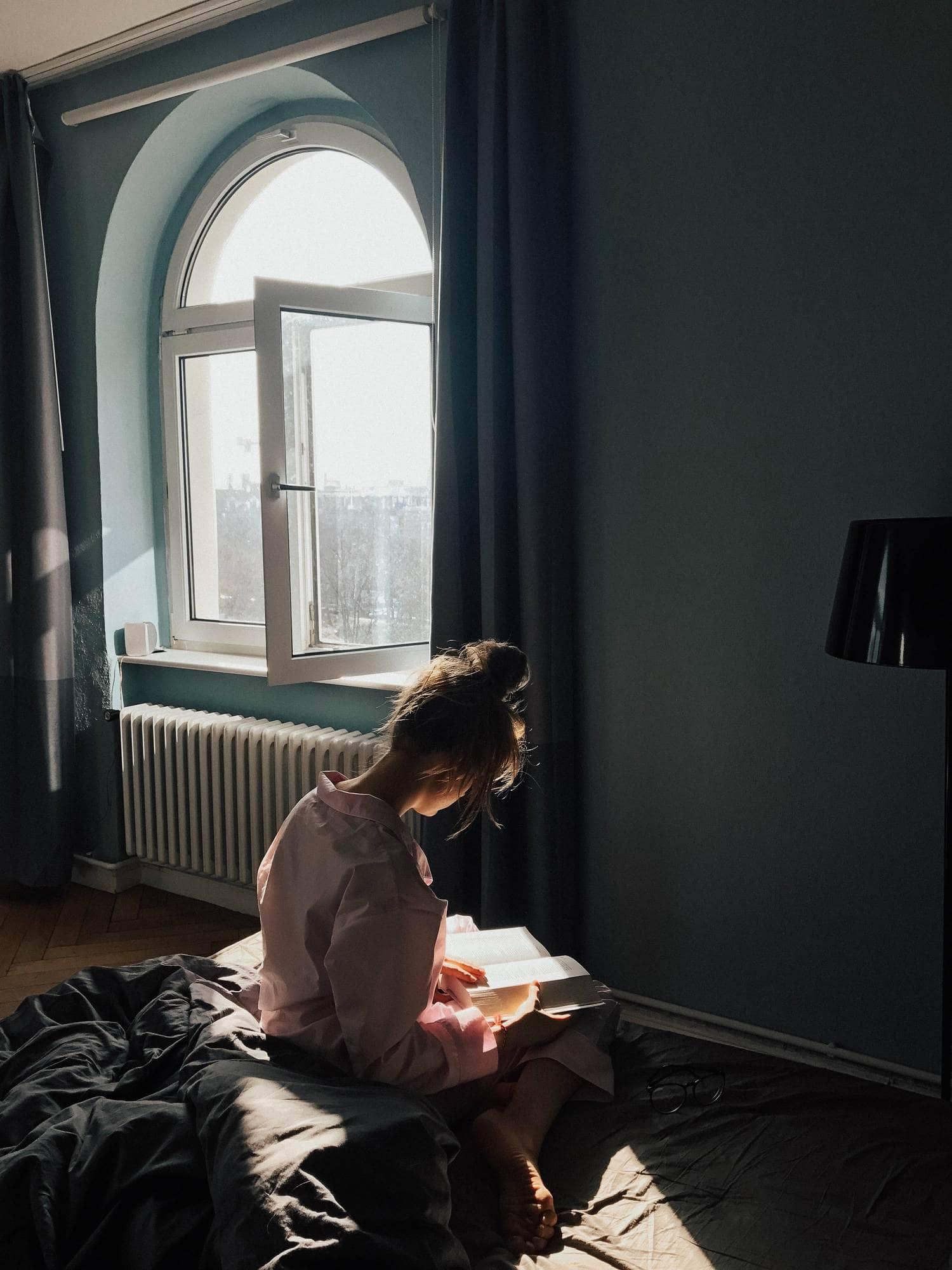 Lectora sentada en la cama bañada por la luz de una ventana
