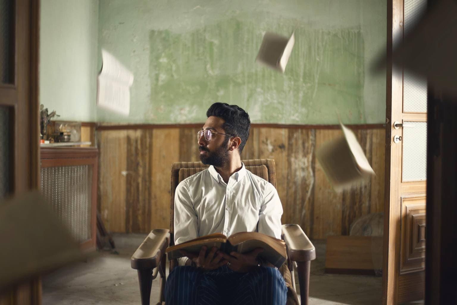 Retrato de hombre en una casa con libros volando