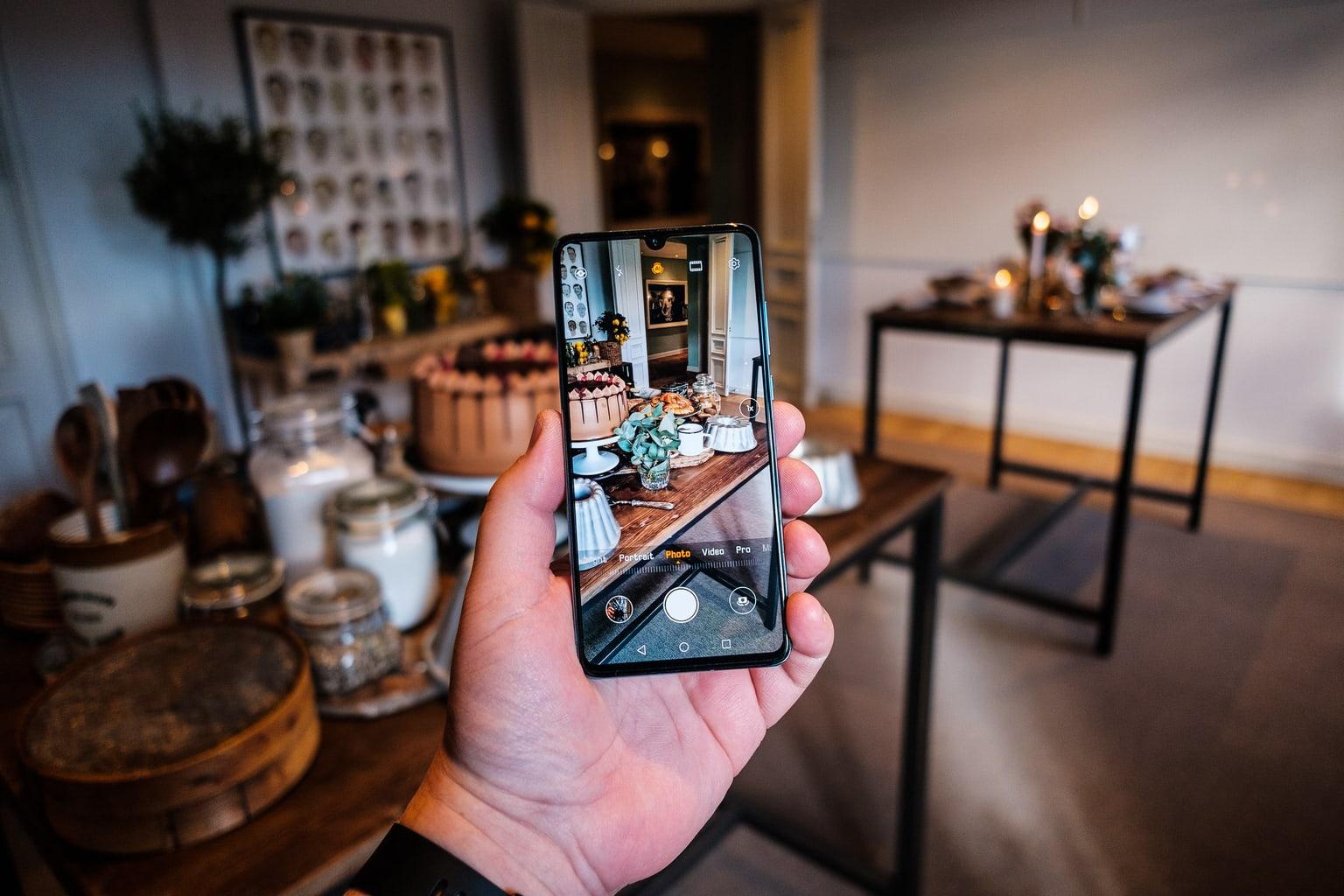 Sosteniendo un Huawei P30 pro en la mano con la vista de cámara enfocando una mesa de comida