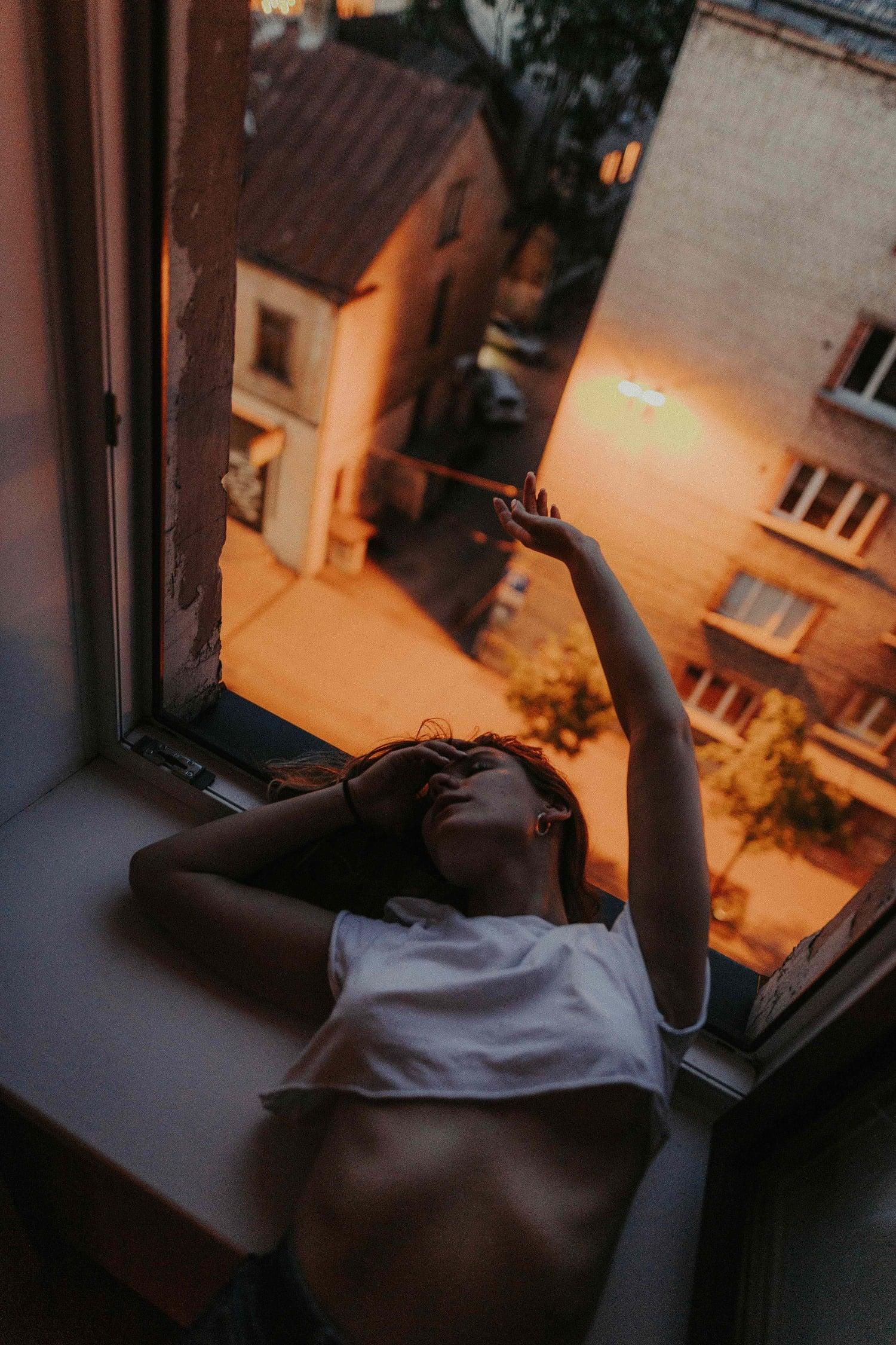 Retrato en la ventana con luz de farolas