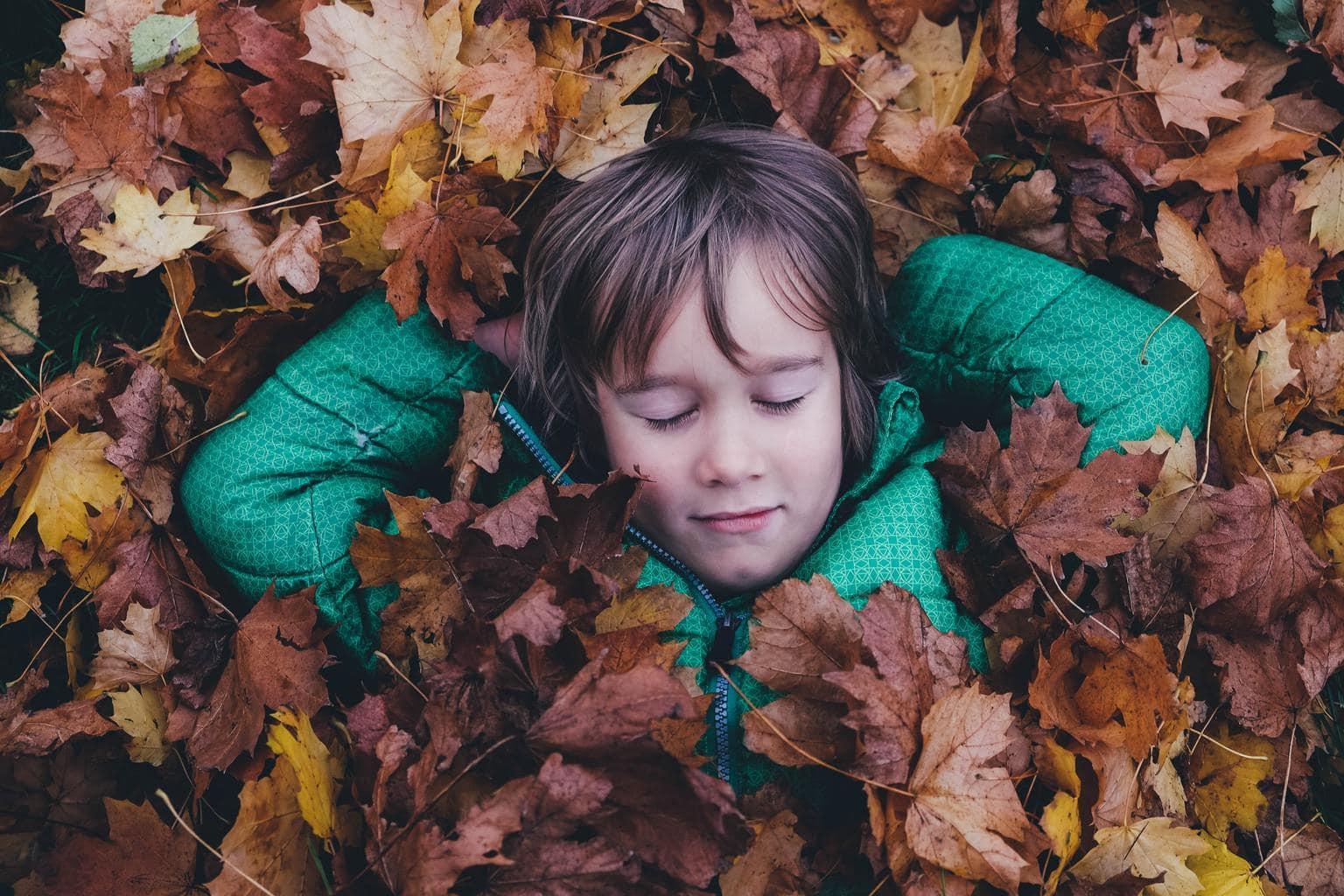 Retrato de niño en perspectiva cenital con fondo de hojas de otoño