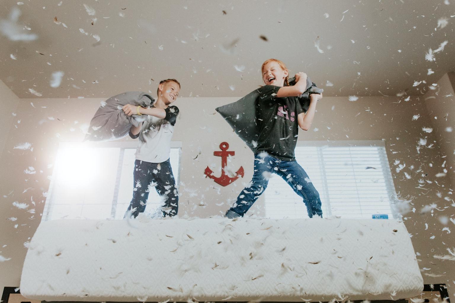 Fotografía que captura el movimiento de niños divirtiéndose con una guerra de almohadas