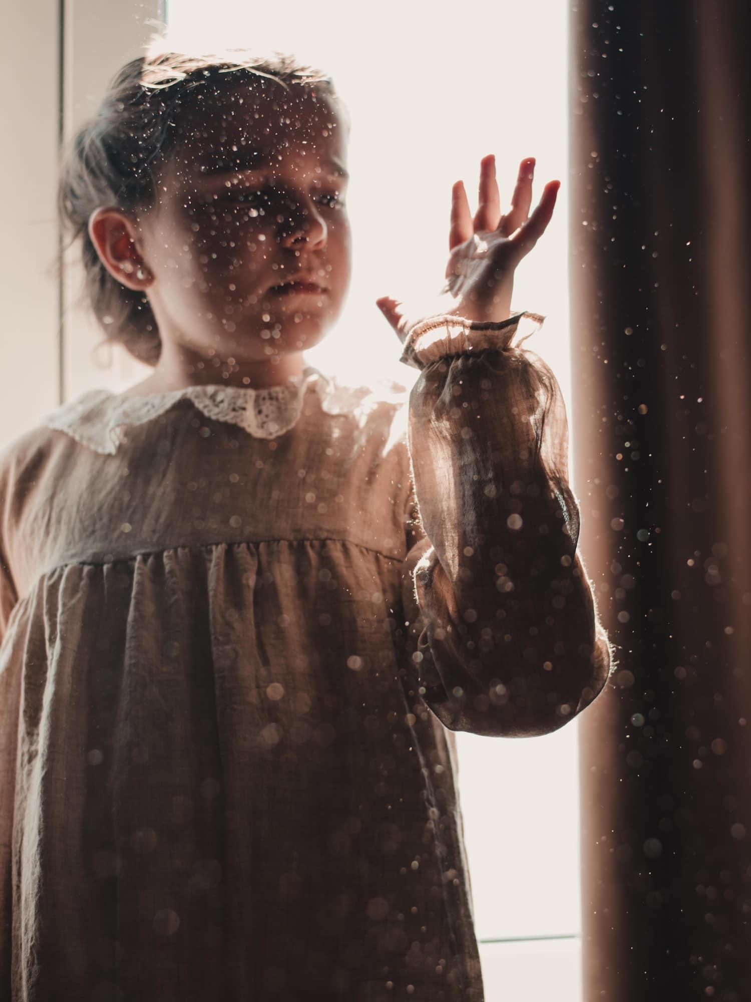 Niña delante de ventana jugando con el polvo en suspensión