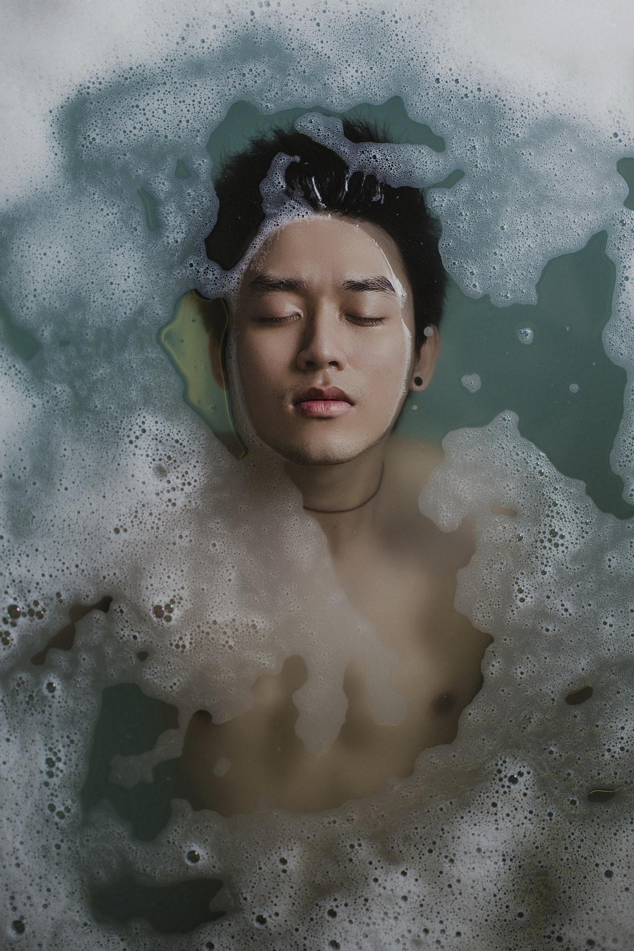 Retrato de chico joven en agua con espuma
