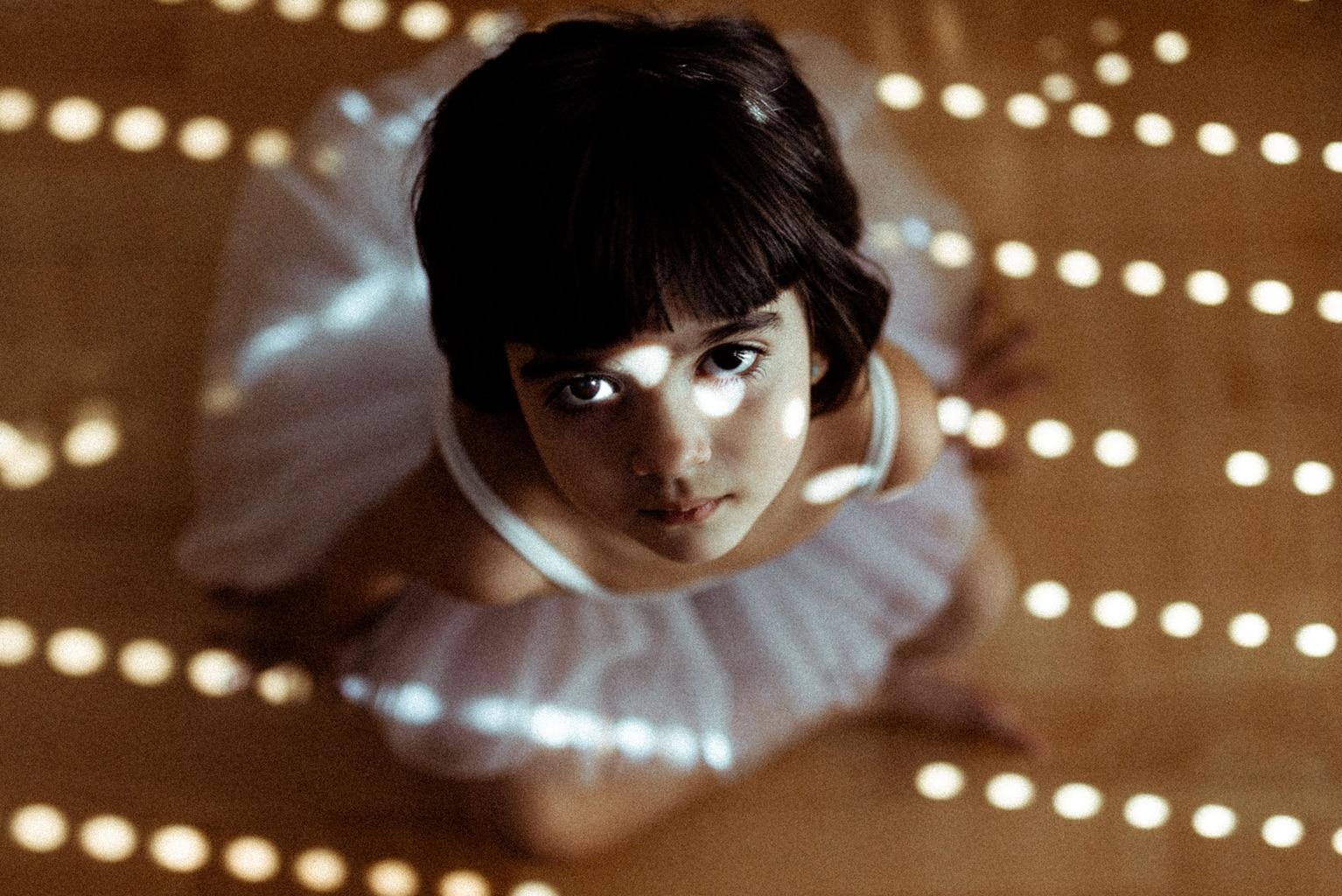 niña vestida de bailarina bañada por la luz de una ventana entre sombras