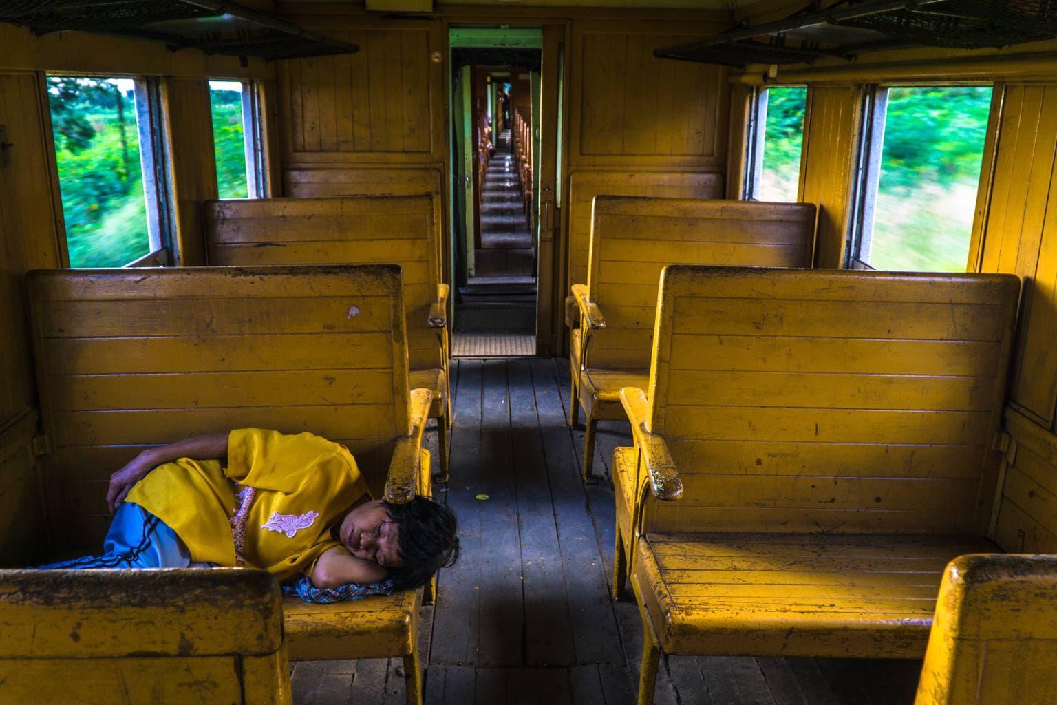 Vagón de tren amarillo con alguien durmiendo la siesta