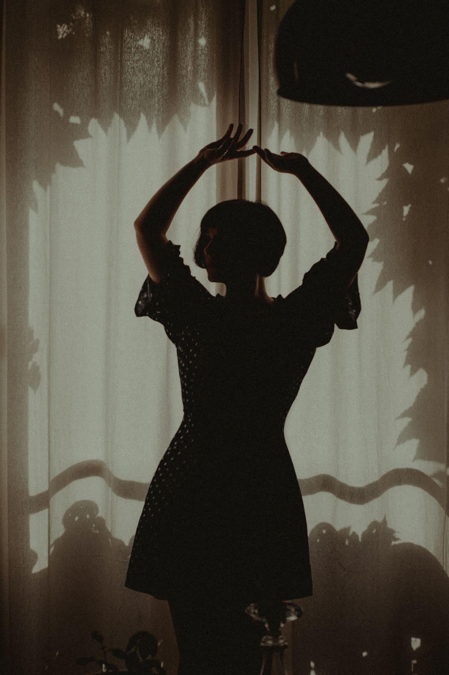Silueta de mujer bailando frente a ventana