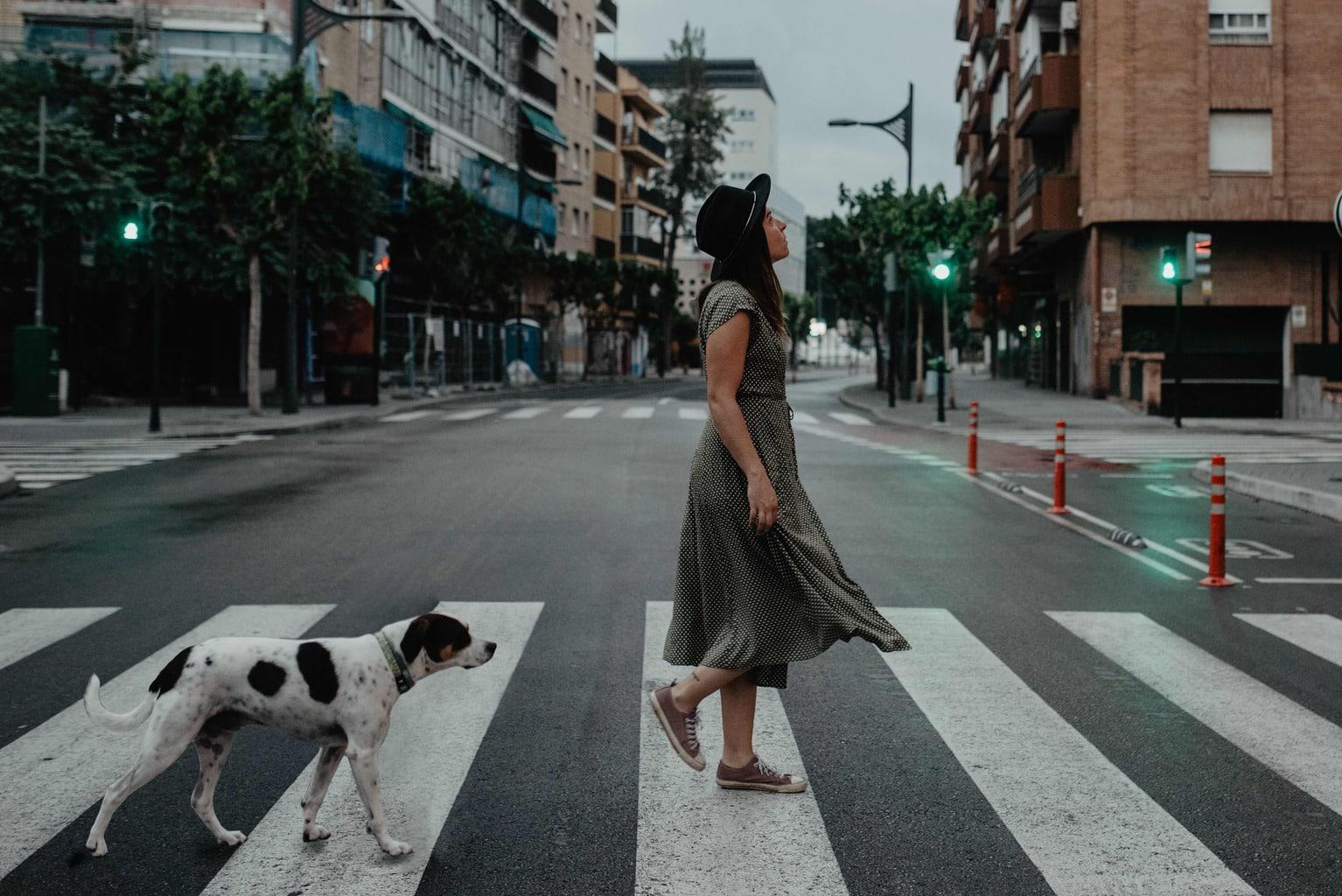 Chica y perro cruzando paso de peatones en autorretrato
