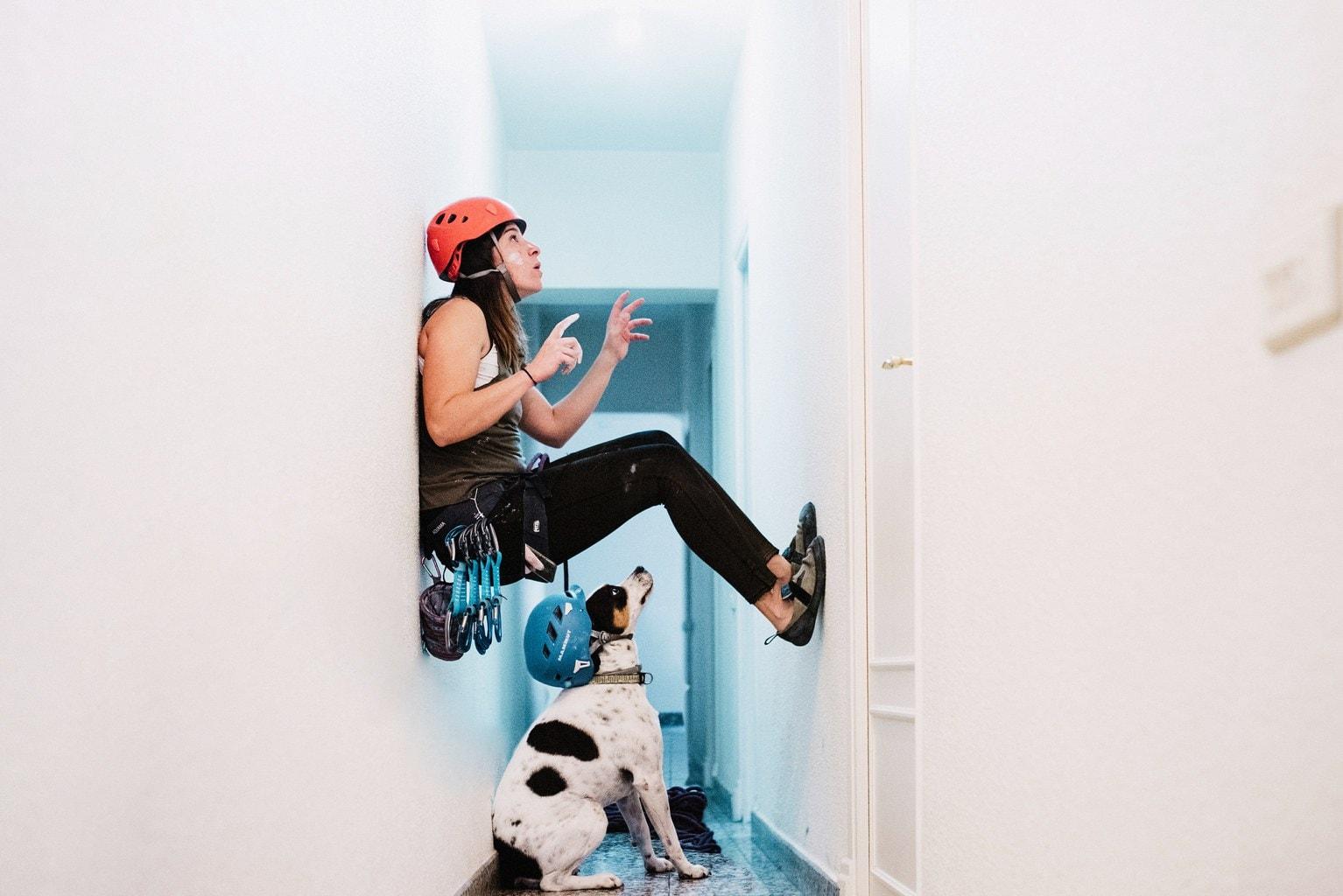 Autorretrato de chica escalando por pared de casa frente a la atenta mirada de su perro