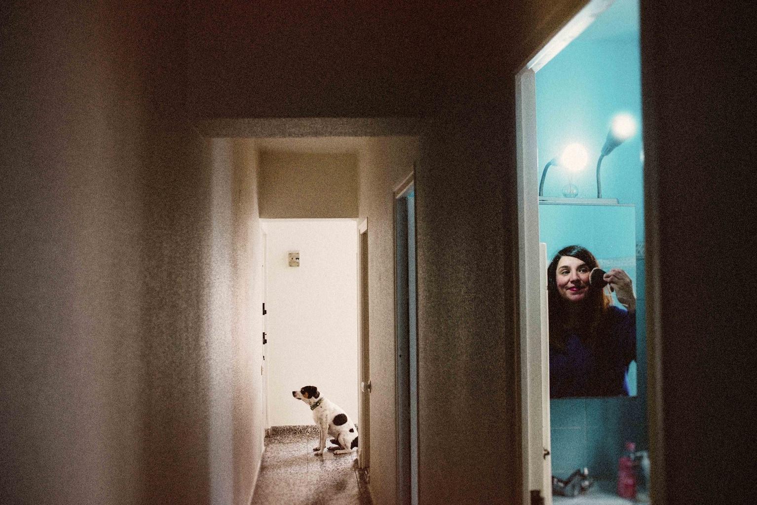 Autorretrato de chica pintándose mientras su perro espera en la puerta para salir