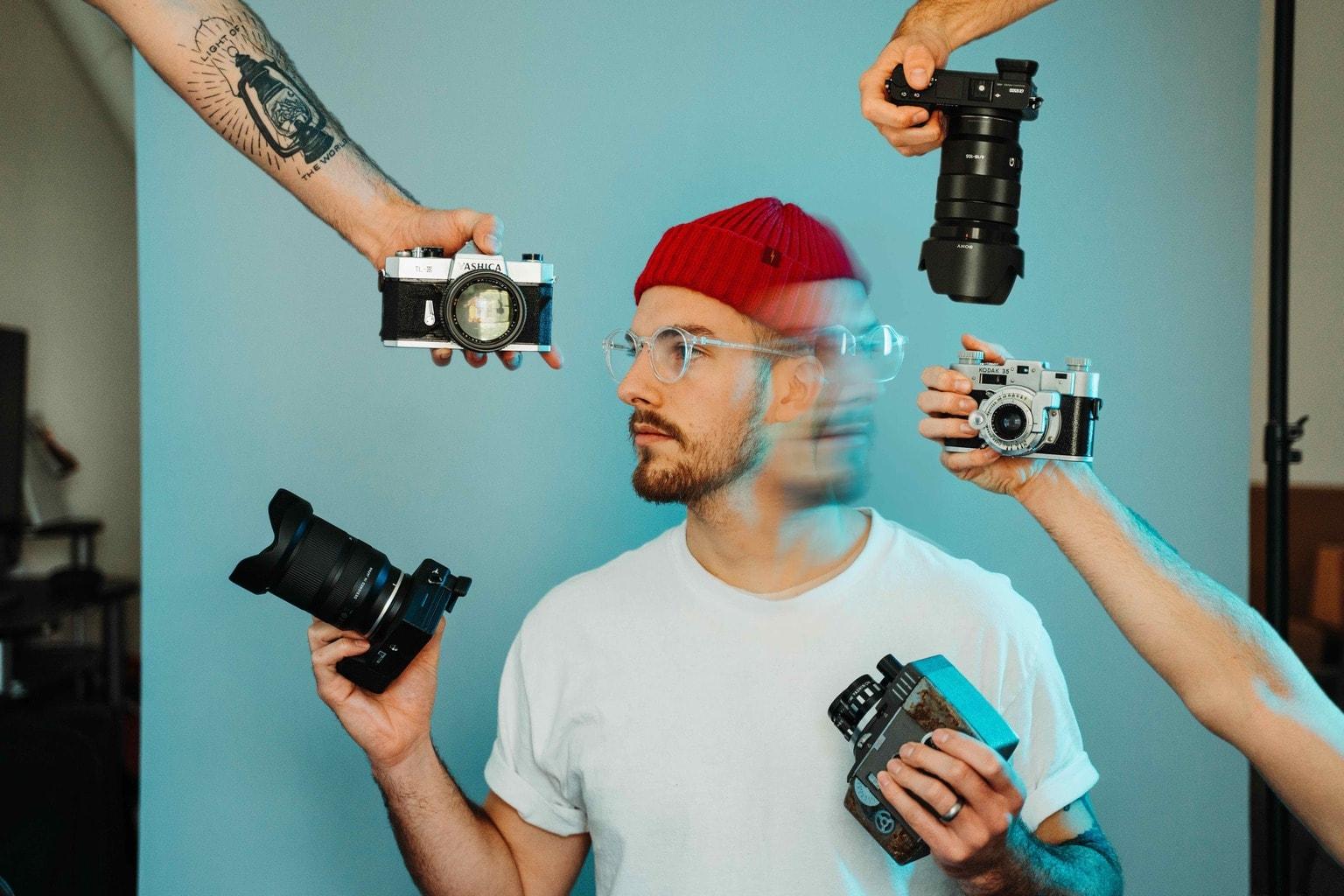 Chico rodeado de diferentes cámaras