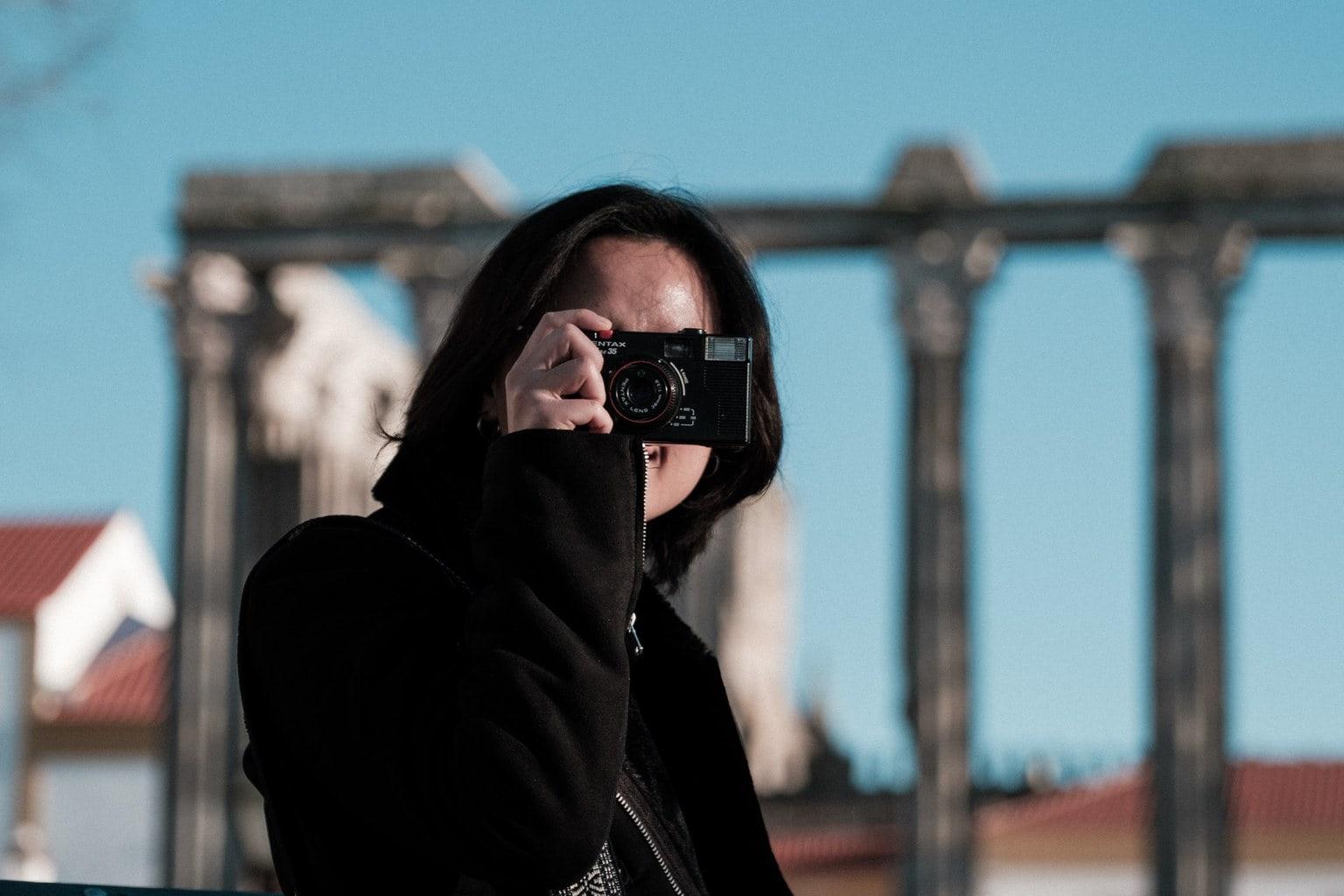 Fotógrafa con cámara y monumento al fondo