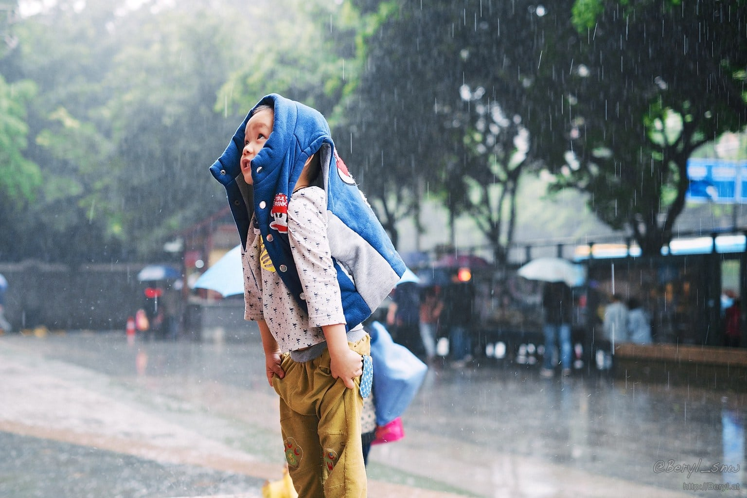 Niño bajo la lluvia fotografiado con desenfoque de 35mm de fujifilm