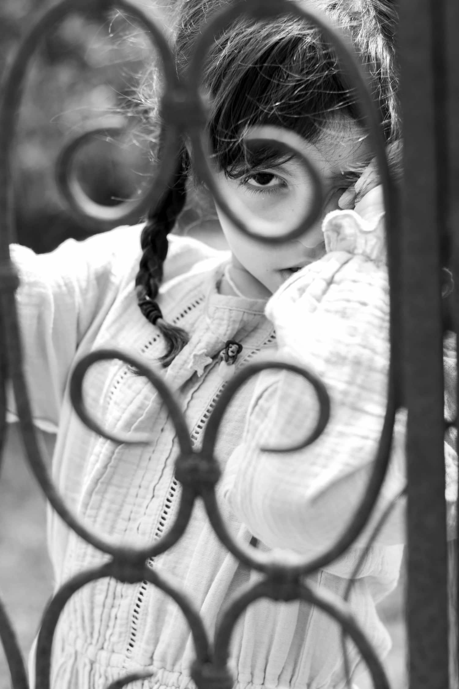 Retrato de niña en blanco y negro detrás de una verja
